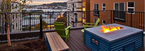 Rooftop deck view from AMLI Mark24 with a flaming firepit and Salmon Bay in the distance under a cloudy evening Seattle sky