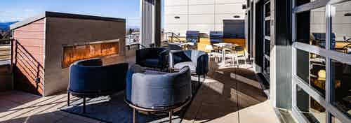 Daytime view of outdoor rooftop lounge with grilling station and blue designer chairs at AMLI Littleton Village apartments