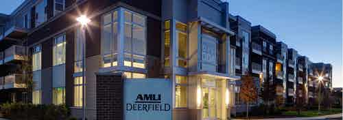Dusk exterior view of the corner of the AMLI Deerfield main building with landscaping and interior lights beaming