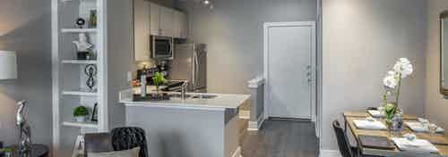 Kitchen and dining room at AMLI Eastside apartments with vinyl wood floors and  white cabinets and stainless appliances