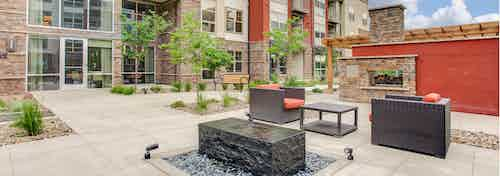 An outdoor fireplace area at AMLI Interlocken apartments with padded chairs and several trees and bushes with blue sky