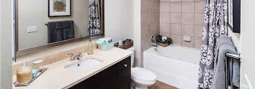 Interior view of AMLI RidgeGate bathroom with travertine countertops and oversized soaking tub with ceramic tile surround