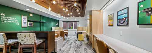 Green wall with wood paneled ceiling and long counter with chairs in resident lounge at AMLI Bellevue Park apartments