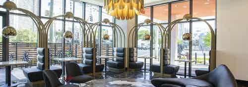 Lobby at AMLI Midtown Miami with black booths along 2 walls of windows with modern couch and large gold chandelier above