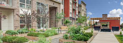 Exterior view of the courtyard at AMLI Interlocken apartments with several planter boxes containing lush greenery and trees