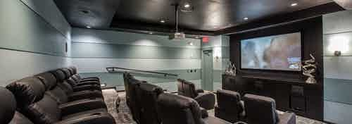 Interior view of media room at AMLI Las Colinas apartment building with three rows of theater seating and large screen
