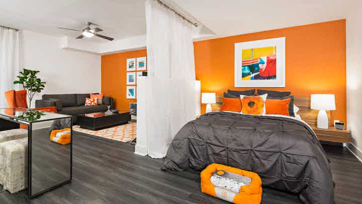 Interior of AMLI Lex on Orange furnished studio apartment with orange wall, queen bed, gray couch and coffee and dining table