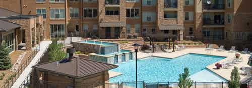 Ariel view of pool at AMLI Inverness apartments with a waterfall feature and surrounding lounge chairs and view of balconies