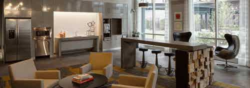 Clubroom at AMLI Lofts with large windows providing city views and a kitchenette with stainless steel appliances and coffee