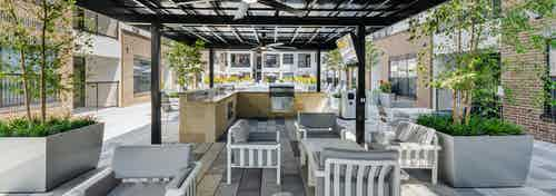 Grill station and outdoor kitchen at AMLI Quadrangle apartments with gray seating and white tables and black cabana overhead
