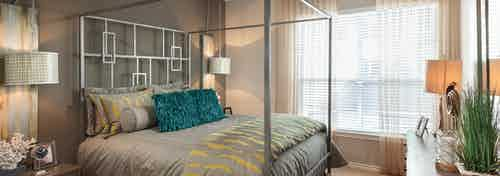Interior view of AMLI Memorial Heights apartment bedroom with silver canopy bed and large window with blinds and curtains