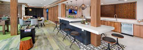 Clubroom at AMLI Decatur with serving kitchen and an arcade game with a poker table and big screen TV on green carpet
