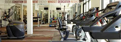 AMLI on Riverside fitness center with a variety of cardio and weight machines and colorful dumbbells visible in background