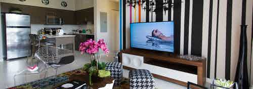 AMLI Dadeland apartment living area with black and white wall, TV on console, hounds tooth stools and a peek into the kitchen