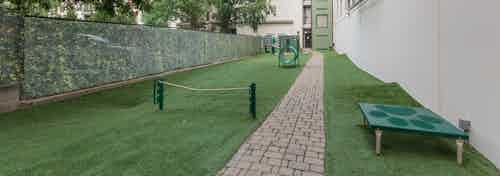 Outdoor grassy paw park next to AMLI Ponce Park apartment building with tunnel and other obstacles for dogs to play with