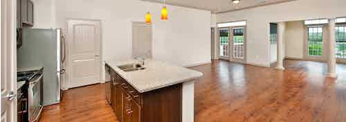 AMLI North Point kitchen with an island and granite countertops with ample free space and pillars in the background