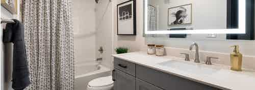 AMLI Quadrangle bathroom with grey vanity and a white countertop with a toilet and shower tub with black and white curtain
