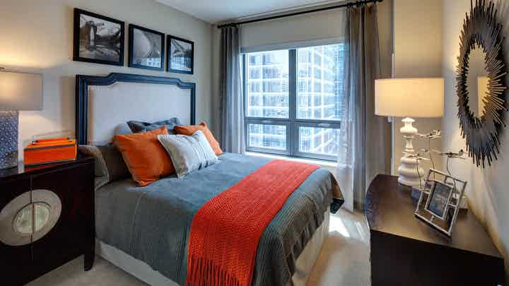 Bedroom at AMLI River North with queen bed with gray and orange bedspread and accent decor with window allowing for natural light