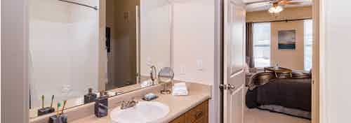 A bathroom at AMLI Inverness apartments with a granite counter top with a stainless steel sink faucet and a large mirror