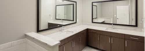 Spacious bathroom at AMLI on Aldrich with a framed mirror above each of the two vanity sinks featured and a white bathtub