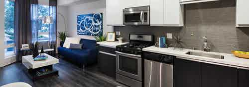 Interior of AMLI Lex on Orange apartment kitchen with white cabinetry and living room with blue couch and hard wood floors