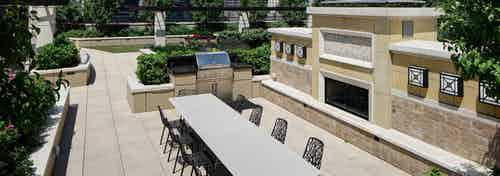Exterior view of AMLI River North rooftop grill area with surrounding vibrant green plants and a long white table with chairs