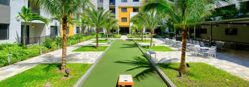 Outdoor courtyard area at AMLI 8800 with green grass, tropical landscape, bocce ball and corn hole games