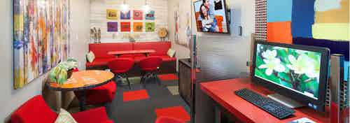 AMLI 300 media room with red couches and chairs, red and black carpet, orange tables, and computer desktops