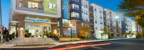 AMLI Piedmont Heights at night showing a well lit entrance with steps leading to front door with sign above and lush greenery