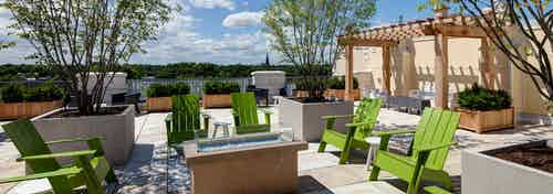 Rooftop deck at AMLI Evanston with grills and lime green lawn chairs next to large potted plants overlooking bright greenery