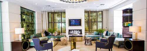 Main resident lounge at AMLI Joya with contemporary living room décor and furniture, electric fireplace and mounted TV