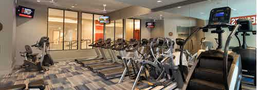 Close up view of cardio machines including a stair climber and multiple treadmills in fitness center at AMLI on Aldrich