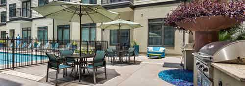 Outdoor grill area next to the pool at AMLI 5350 with table and chair sets with tan umbrellas and large stainless steel grill
