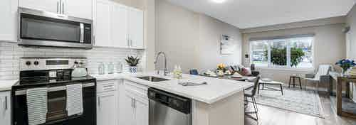 Interior of a AMLI Bellevue Park apartment kitchen with stainless steel appliances and white cabinets and view of living room
