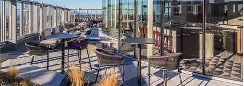 Exterior deck of AMLI Arc with seating and fire pit and views of Seattle