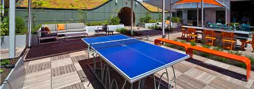 A beautiful sunny day of a blue ping pong table on AMLI South Lake Union rooftop deck with patio seating and fire pit