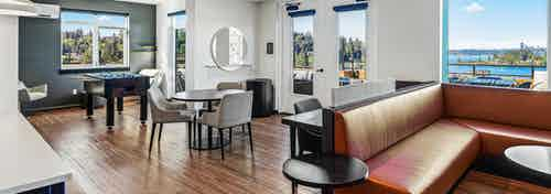 AMLI Bellevue Park sky lounge with brown leather couch and table and chairs and large windows with view of Lake Washington