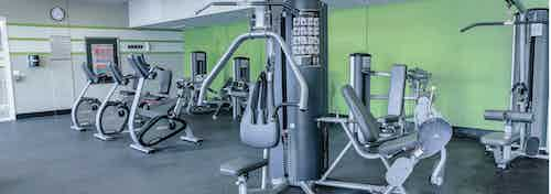 Interior view of a fitness center AMLI Arista apartments with strength training machines stationary bicycles and green walls