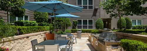 AMLI River Oaks outdoor grilling and dining area with a gas grill surrounded by lush greenery and shaded by blue umbrellas