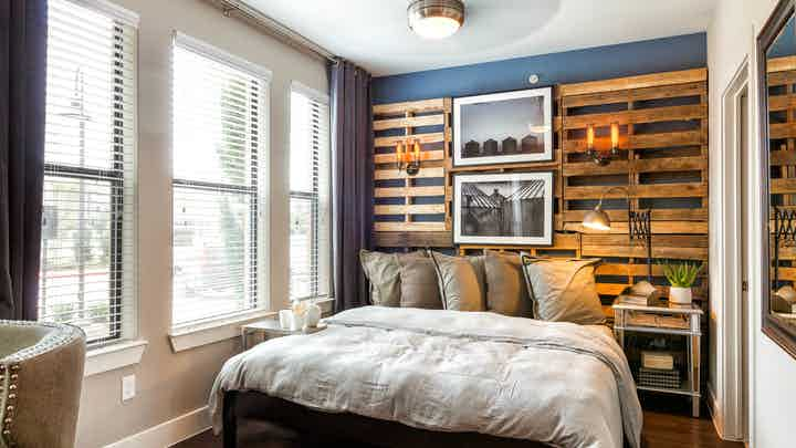 Interior view of AMLI Campion Trail studio apartment bedroom area with bed and night stand and large windows
