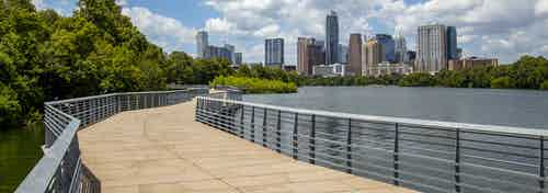 Lakefront boardwalk with metal railings by AMLI South Shore apartments with views of downtown Austin skyline and lush greenery