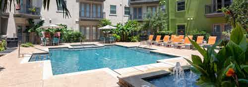 Exterior view of daytime AMLI 300 resort-style swimming pool with gas grills, lush greenery, and poolside dining