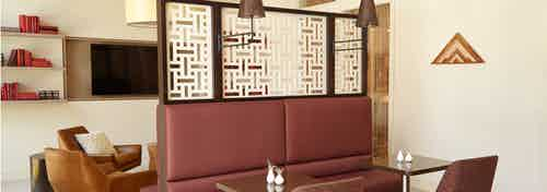 AMLI on Riverside resident lounge showing burgundy booth seating at two small tables with couch seating and flat screen TV