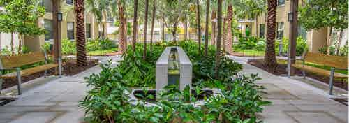 Exterior view of lush landscaped courtyard at AMLI Dadeland with park benches and a tranquil fountain in the center