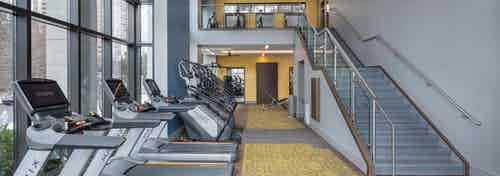 Fitness center at AMLI 3464 with yellow carpet and treadmills near tall windows with a modern staircase in the background
