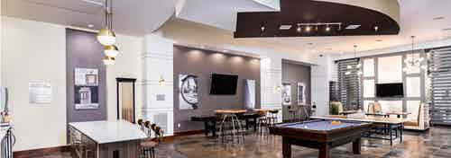 Interior view of the club room at AMLI Park Avenue apartments with a pool table and multiple seating areas and wall art work