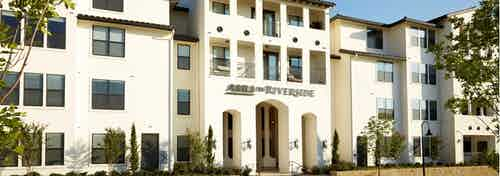 Exterior of AMLI on Riverside white stucco building facade with small trees lining the entry way and larger trees nearby