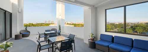 AMLI 8800 exterior skyline view of the rooftop terrace with table and chairs and blue sofa seating area