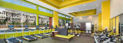 Interior of fitness center at AMLI Buckhead with vibrant yellow walls and large windows in front of a line of treadmills