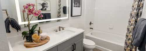 AMLI Quadrangle bathroom with a grey wood vanity sink with a white countertop next to a toilet and a white tiled shower tub